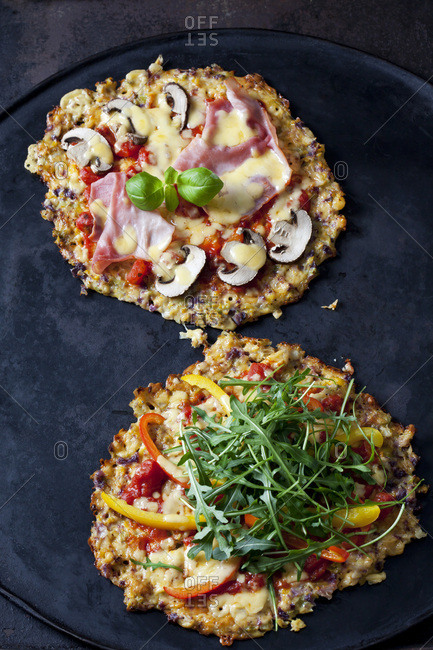 Cauliflower pizza garnished with rocket and bell pepper and champignons and cooked ham