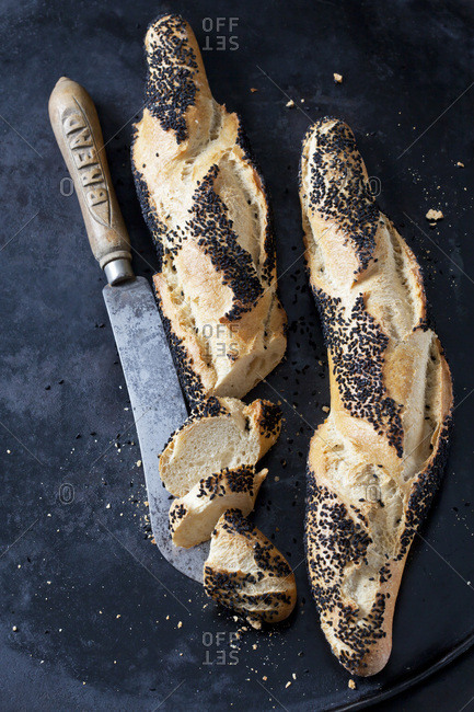 Two baguettes with black cumin and a bread knife on dark metal