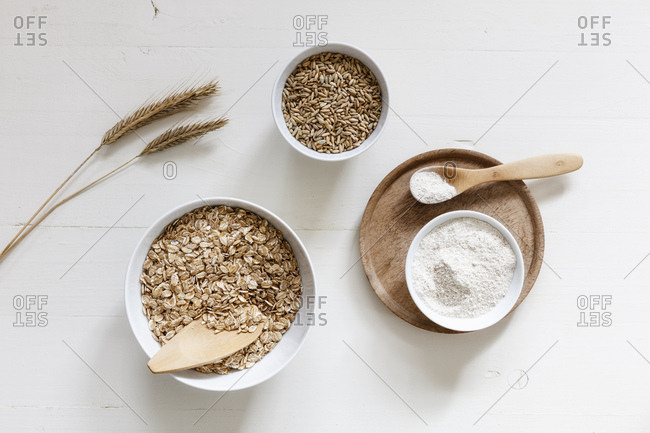 Rye ears and bowls of rye flakes- rye flour and rye grains on white background