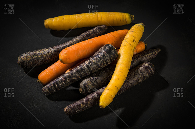 Various sorts of carrots on dark ground
