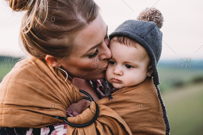 Mother kissing baby in carrier