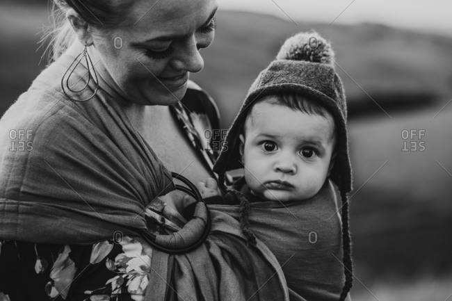 Mother with baby in carrier in black and white