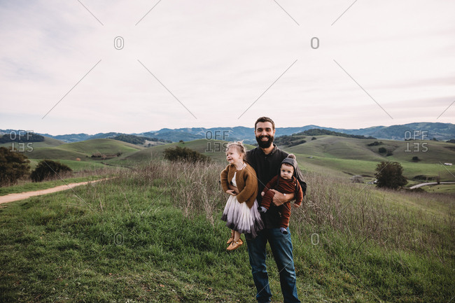 Father holding two children on a mountaintop