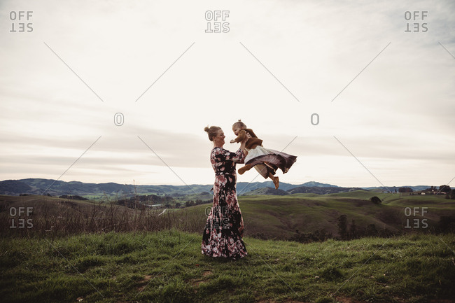 Mother spinning young daughter on mountaintop