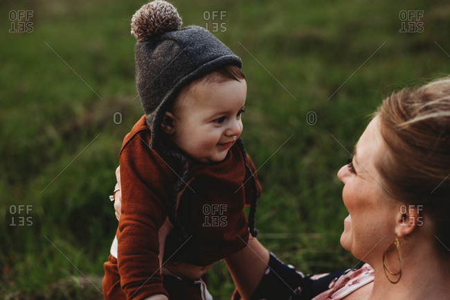 Mother looking at baby son in hat