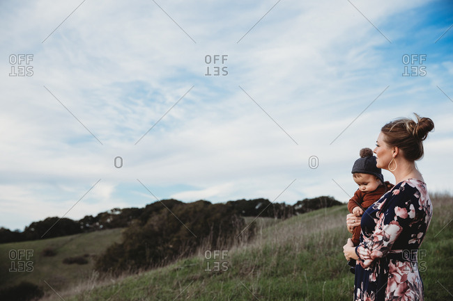 Mother holding baby on mountain hillside