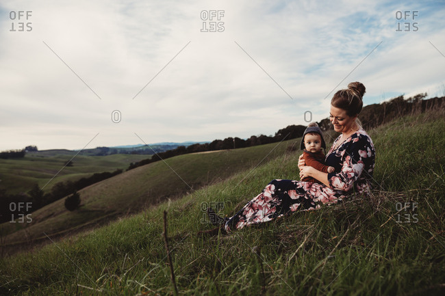 Mother holding baby while sitting on mountain hillside