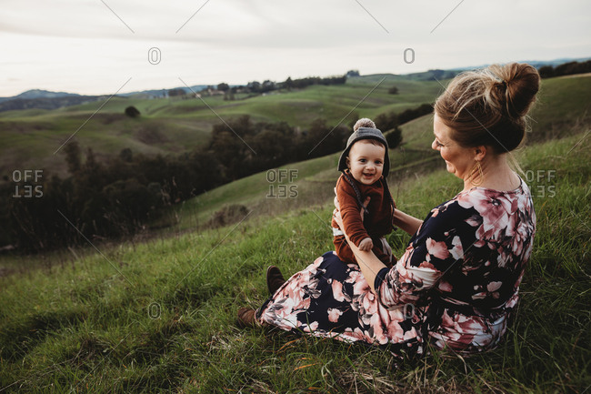 Mother smiling at young baby boy in hat on mountain hillside