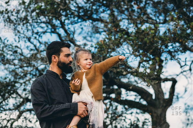 Father holding daughter by a tree