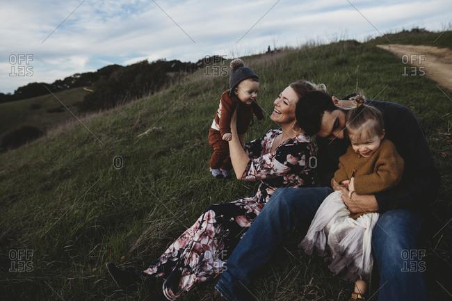 Family sitting on hillside together