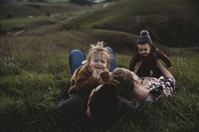 Family lying on hillside together