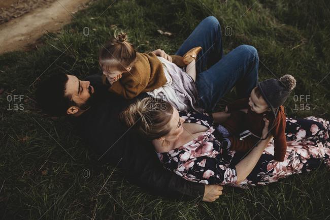 Family lying on grassy hillside together