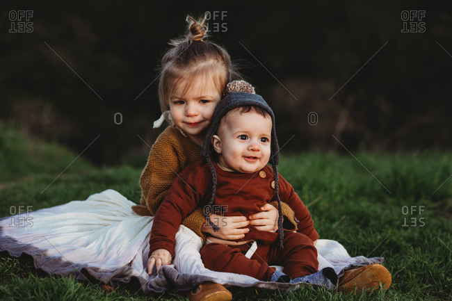 Young girl holding baby boy in her lap