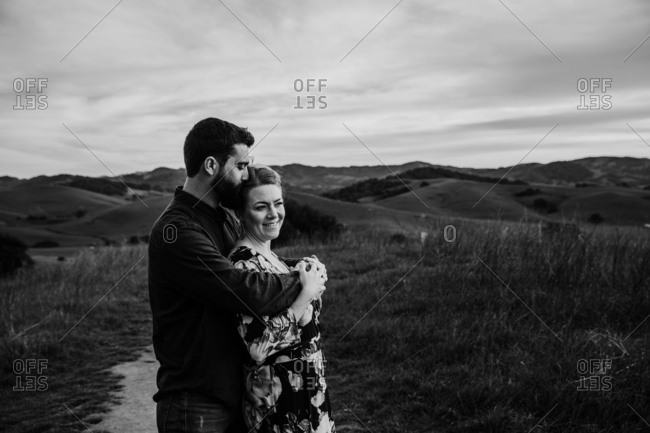 Couple embraced on top a mountain in black and white