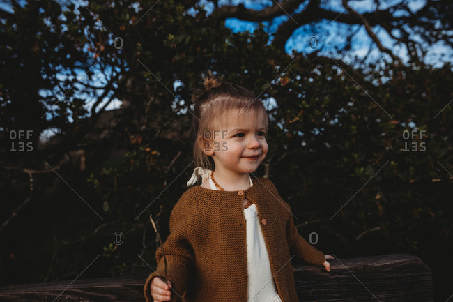 Young girl holding stick and smiling