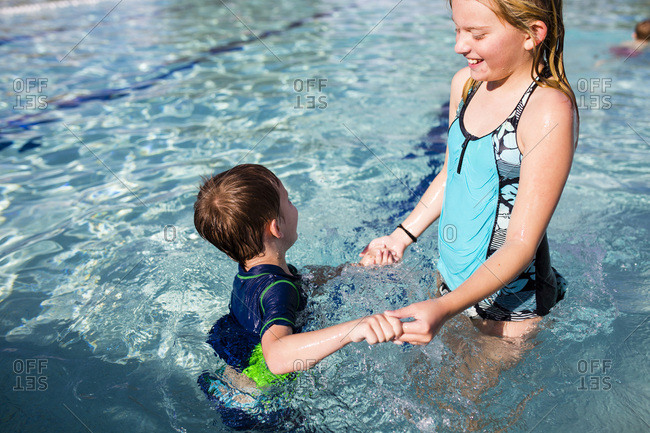 Young girl playing with little brother in swimming pool