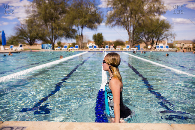 Young girl standing near edge of swimming pool
