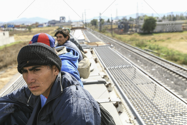Mexico - November 07, 2007: Young migrants riding on roof of train hoping to cross border into United States of America