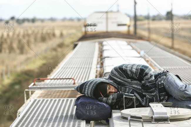 Mexico - November 07, 2007: Young migrant sleeping on roof of train hoping to cross border into United States of America