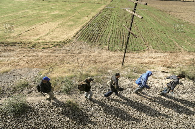 Celaya, Mexico - November 08, 2007: Migrants walking along train tracks looking for next train to take them to border with United States of America