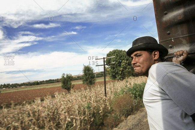 Celaya, Mexico - November 08, 2007: Young migrant holding onto wagon on train hoping to get to border with United States of America