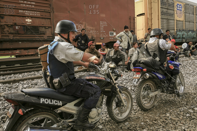 Celaya, Mexico - November 08, 2007: Armed police on motorbikes ride by group of migrants sitting on train tracks hoping to get to border with United States of America