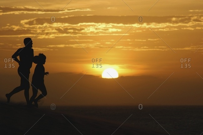April 6, 2018: Father And Son Running On Sand Dunes At Sunset, Jericoacoara, Brazil