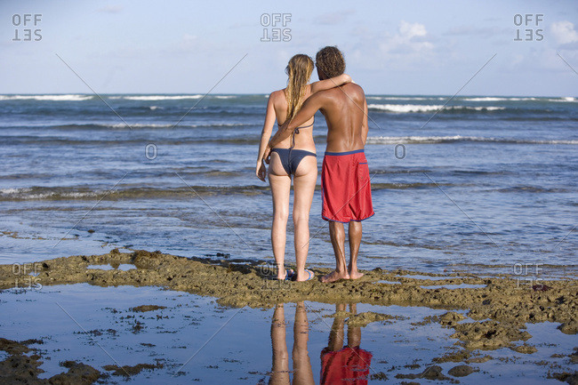 April 6, 2018: Couple In Swimwear Embracing Looking At Ocean At Praia Do Forte, Bahia, Brazil