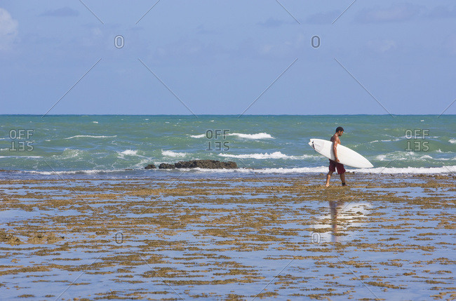 April 6, 2018: Man Carrying Surfboard At Praia Do Forte, Bahia, Brazil