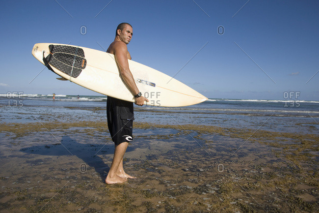 April 6, 2018: A Surfer With His Surfboard At The Beach, Praia Do Forte, Bahia, Brazil