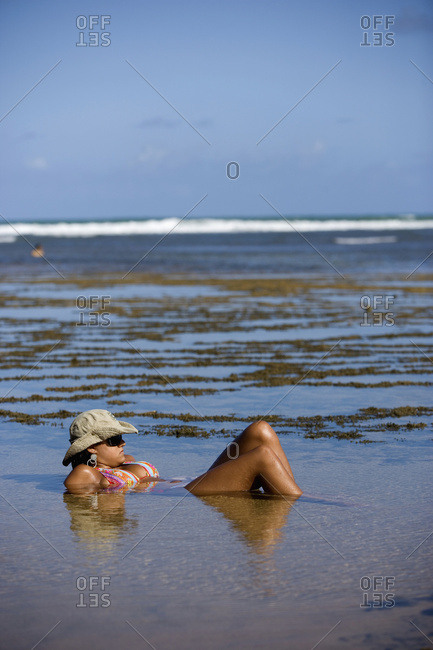 April 6, 2018: Woman Lying Partially Submerged In Rockpool, Praia Do Forte, Bahia, Brazil