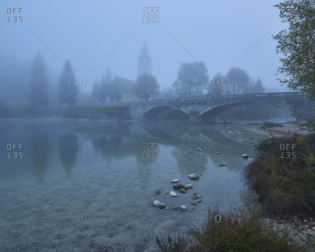 Church of St. John The Baptist on the banks of Lake Bohinj in morning mist, Triglav National Park, Slovenia, Europe