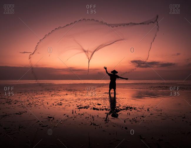 Sunrise fisherman casting his net, Bali, Indonesia, Southeast Asia