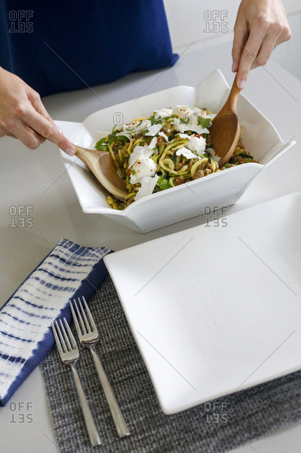 High angle view of woman mixing vegetables ready to serve