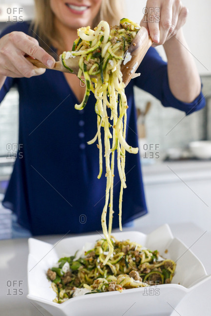 Close up of woman serving a dish of zucchini noodles