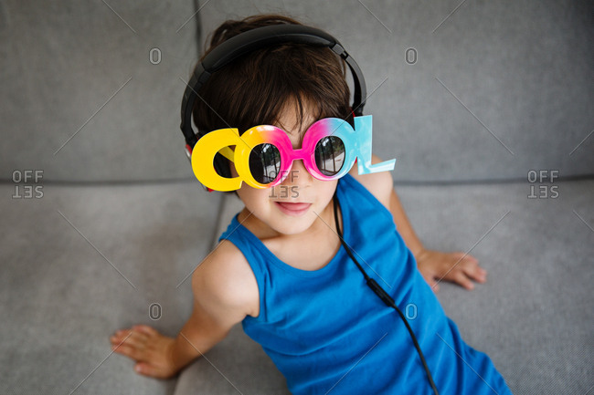 Portrait of little boy on couch wearing novelty sunglasses and headphones