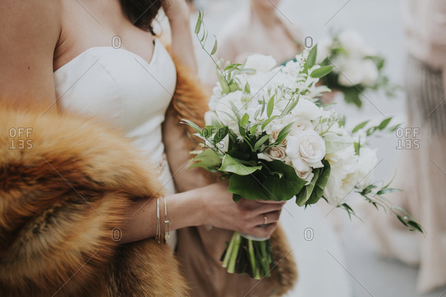 Columbus, Ohio  - January 28, 2017: Midsection of bride with fur holding bouquet during wedding ceremony