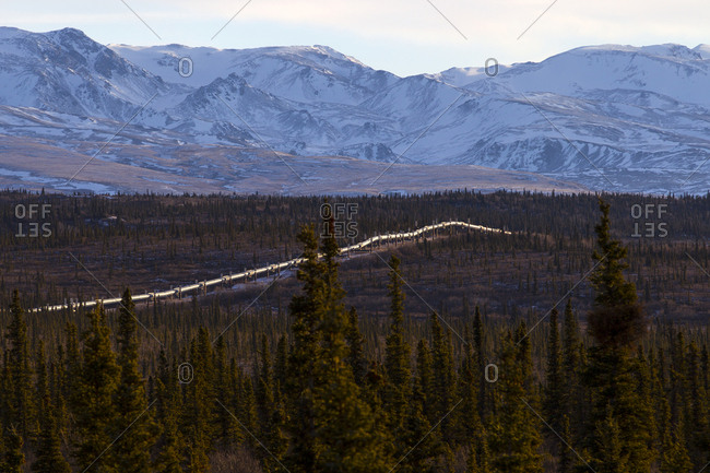 Alaska, USA - November 4, 2013: High angle view of Trans-Alaskan Pipeline amidst trees against mountains during winter