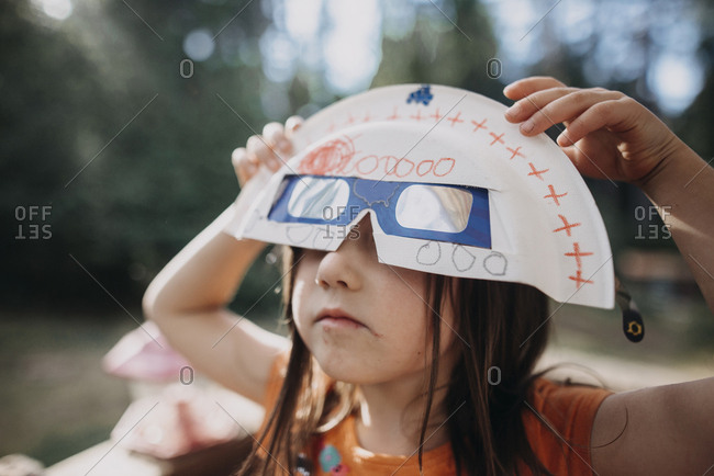 Girl holding solar eclipse glasses and mask while playing at park