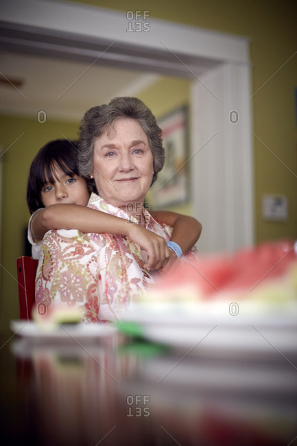 Portrait of granddaughter standing by grandmother at home