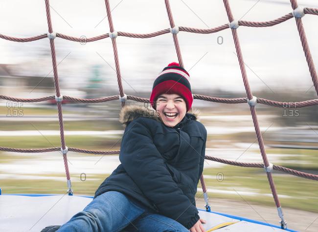 Happy boy enjoying in merry-go-round at playground