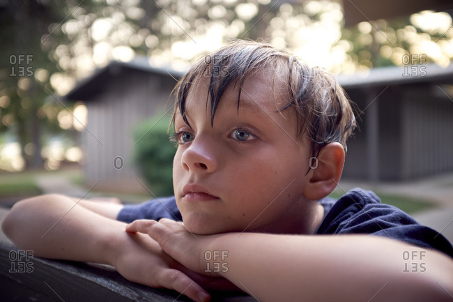 Close-up of thoughtful boy looking away while leaning on bench at park