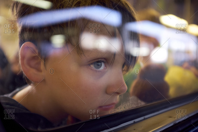 Boy looking through window while traveling in train seen through glass
