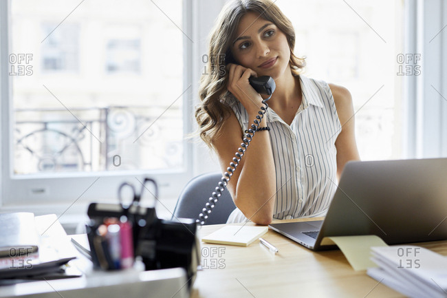 Businesswoman answering telephone while working at desk in office