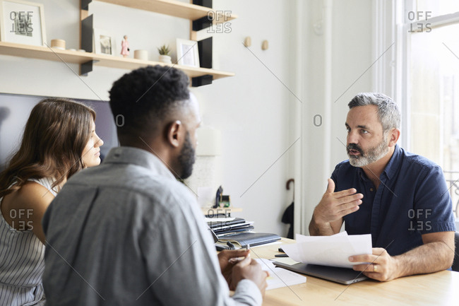 Businessman explaining documents to colleagues in creative office