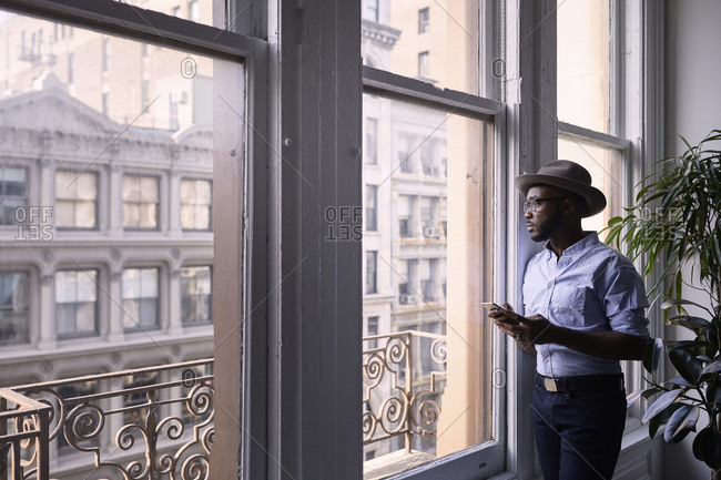 Businessman using mobile phone while standing by window in creative office