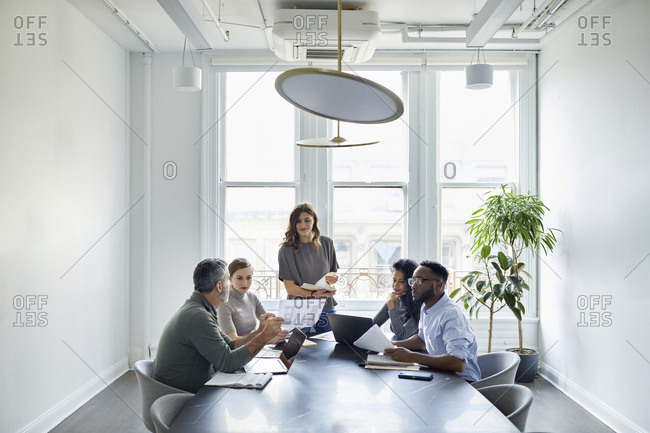 Businessman discussing documents with colleagues in conference room at creative office