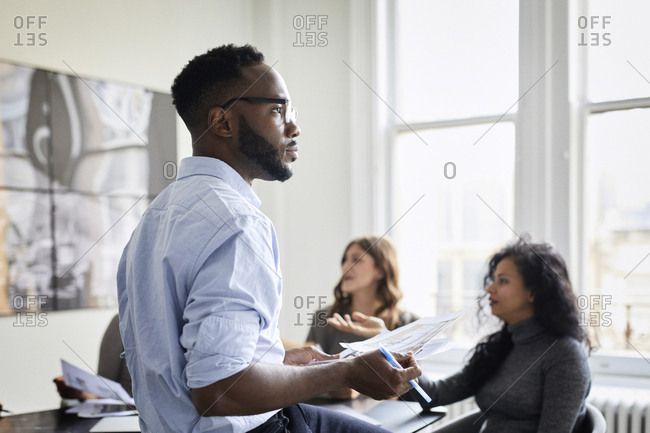 Thoughtful businessman holding documents while female colleagues discussing in creative office