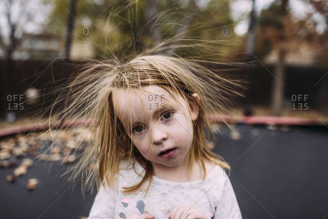 Portrait of cute girl with tousled hair against trampoline at park during autumn
