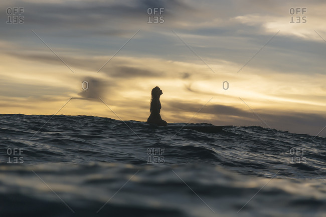 Mid distance view of silhouette young woman in sea against cloudy sky during sunset